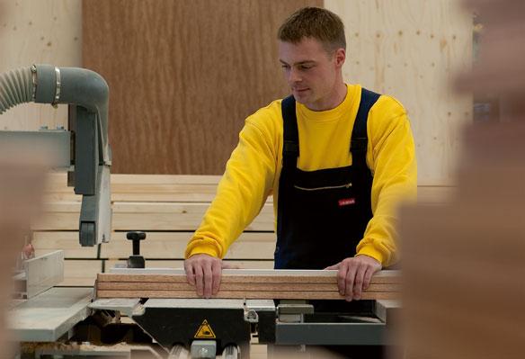 Arbeiter schneidet Holz zu
