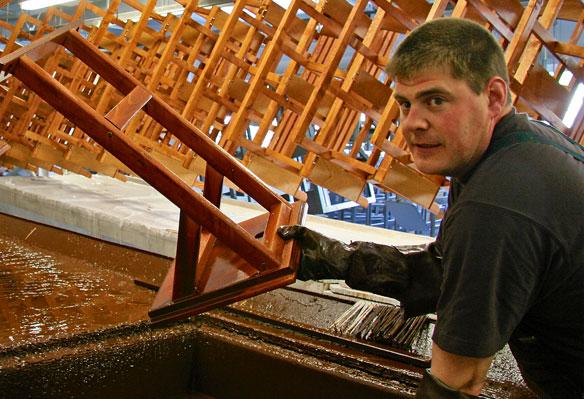 Arbeiter taucht Holzteil in Farbe