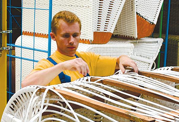 Arbeiter flicht den Oberkorb eines Strandkorbs
